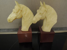 Two horse head bookends made of alabaster marble powder with red bases