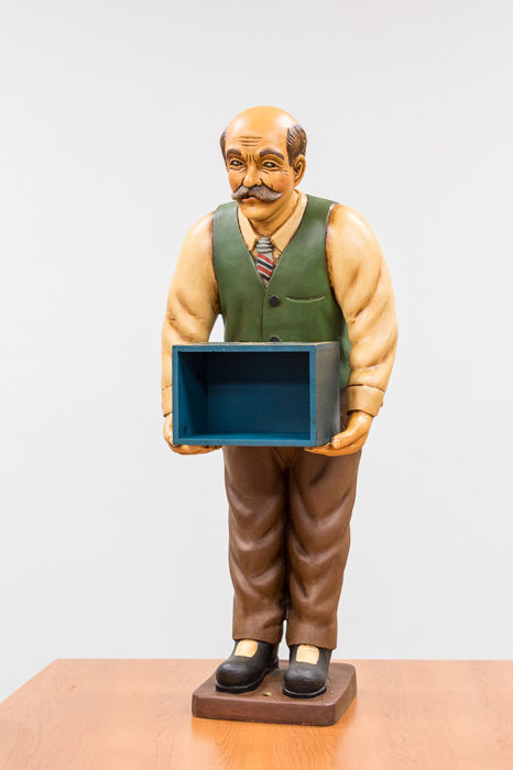 Beautiful sculpture of an elderly man with a storage box