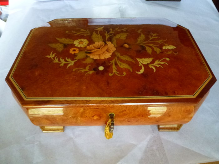 Fabulous jewellery case with solid lacquered wood music box, camphor coloured with central floral design - with luxurious interior, finished in amaranth velvet. Includes a music box with the island of Capri as motif, the lock and hinges are golden coloured.