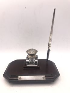 Crystal inkwell with decorated silver lid and neck, in a mahogany wooden holder, including a silver dip pen