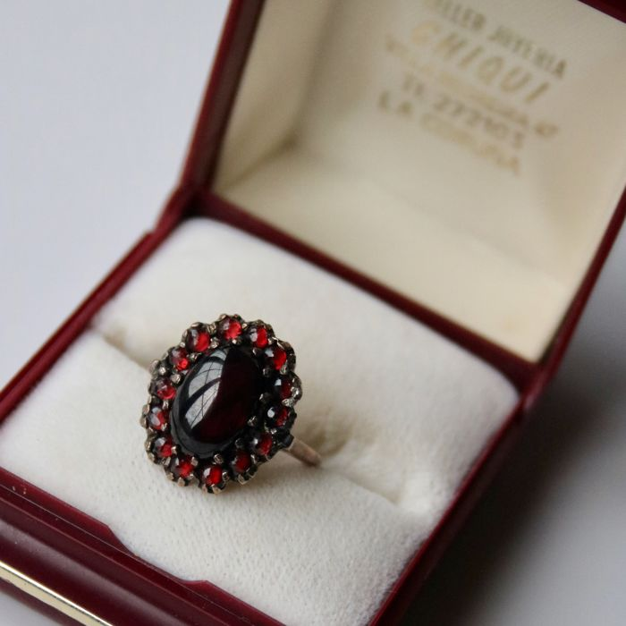 Wonderful handcrafted entourage ring with a large cabochon Garnet 10X7.3mm and round cut Garnets ca. 2.8mm each. Excellent state.
