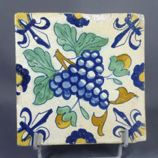 Tile in polychrome faience decor of a bunch of grapes,
