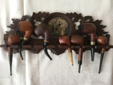 Hand carved Art Nouveau oakwood pipe rack with 18th century print. A cigar box of Eminent 7 pipes of various brands, partly trimmed with silver, horn, bakelite and various wood types - 1st half of 20 century.
