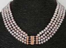 4-strand natural-coloured freshwater pearls with a 14 kt gold clasp
