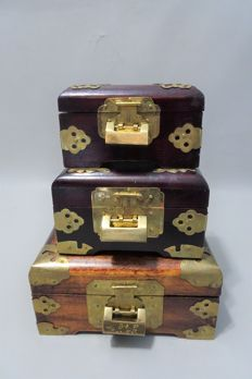 Three wooden jewellery boxes with copper hardware and inlaid with hard stone amulets, of which 1 with music box.   - China - 2nd half 20th century