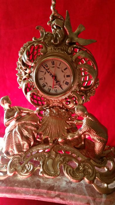 Romantic clock in alloy of bronze, with a carved figure of a lady and a gentleman, portraying a marriage proposal, in a beautiful enchanted garden, French style, 20th century