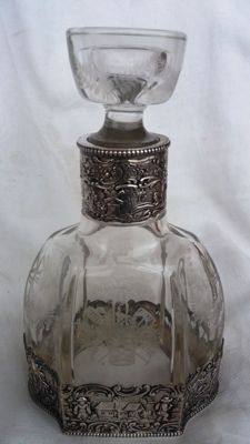 Victorian Bottle, with base and collar in chiselled and embossed silver - Complete with stopper - carved glass. 20th century