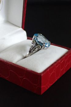 Silver women's ring with a large blue topaz and floral shank