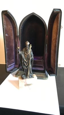 A bronze sculpture of Saint Augustine in a portable altar