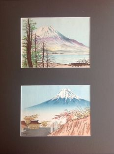 Two woodblock prints depicting a snow-covered Mount Fuji, set in a beautiful dark grey passe-partout - Japan - around 1950