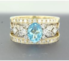 14 kt bi-colour gold ring with harp pattern, set at the centre with a blue topaz and 34 brilliant cut diamonds, approx. 1.70 ct in total.