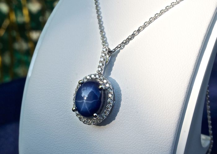Superb oval starry cabochon sapphire, 5 ct, certified natural by EGL laboratory (India), in pendant on 18 kt white gold necklace, with hinged pendant ring and entourage of GH-SI natural diamonds, brilliant cut for 0.26 ct in total.