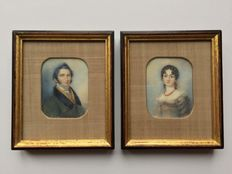 A pair of miniature portraits of a Lady wearing a lilac dress and coral necklace and a Gentlemen wearing a green coat, German school, circa 1820
