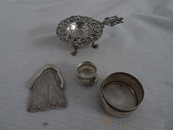 Collection of 5 pieces of silverware, including little purse tea strainer with drip tray and 2 napkin rings