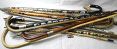 Collection 12 canes of which 8 are decorated with souvenir plaques from brass and/or metal