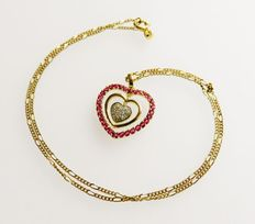 Gold heart pendant with rubies and diamonds totalling 1.18 ct on a gold necklace / figaro necklace