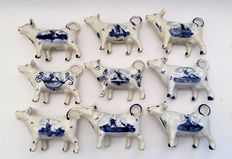 "Collection of 9 monochrome porcelain Cow creamers ""Handpainted Delft Holland"""