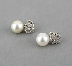 White gold earrings set with brilliant-cut diamonds in a flower-shaped setting and South Sea Australian pearls measuring 10.7 mm.