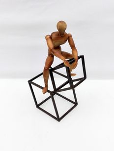 An abstract wooden figure on a metal stand