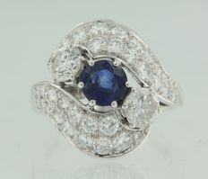 Platinum ring set with a brilliant cut sapphire in the centre with an entourage of brilliant cut diamonds around it.