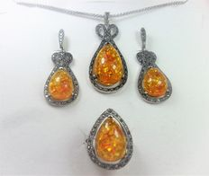 Silver jewellery set consisting of ring, earrings and pendant with orange amber and marcasites