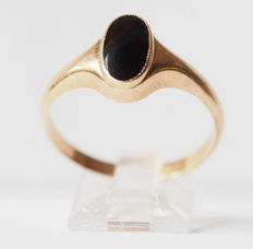 Yellow gold women's ring with oval, smooth cut black stone