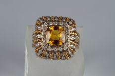 Gold ring with central yellow sapphire and diamonds