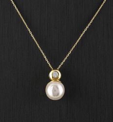 Yellow gold chain and yellow gold pendant set with a diamond and an Akoya pearl.
