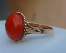Heavy ring with a cabochon of natural red coral on 18 kt yellow gold