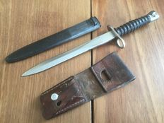 Original Swiss bayonet with an original leather holder to attach to the belt.