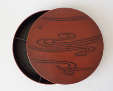 Large red varnished round bento box with a black varnished relief. Including matching storage case - Japan - approx. 1950
