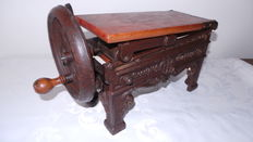 Cast iron cutting machine with feeding mechanism and wooden tray.