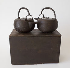 Set of 2 cast iron sake kettles (chōshi). With rabbits and bamboo in relief, and varnished wooden lids. With the original storage box – Japan – 1828 (Edo period)