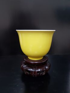 Monochrome yellow bowl with wooden stand - China - late 20th century