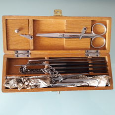 Rare surgical emergency instruments in a wooden box.