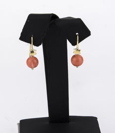 Yellow gold earrings with a star-shaped motif and a Pacific coral bead on each