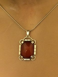 Silver pendant with cabochon cut amber on a chain.