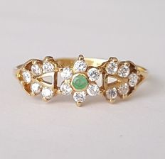 Gold ring with emerald and zirconias