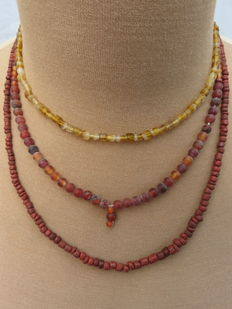 Late Medieval necklaces with yellow glass and carnelian beads - 41 cm, 45 cm and 52 cm. (3)