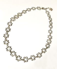 A silver necklace with pendant on the clasp