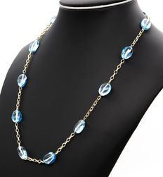 Yellow gold necklace with 12 oval-shaped blue topaz gemstones.