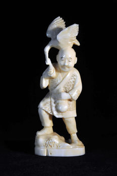 Small ivory okimono of a man with a bird - Japan - early 20th century