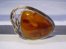 An antique brooch with big natural amber