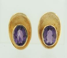 18 kt yellow gold clip-on earrings set with an oval cut amethyst, height 2.3 cm.