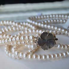 Beautiful 3- row necklace with genuine cultured shiny pearls and large zilver lock with decorative flower. Very good condition.