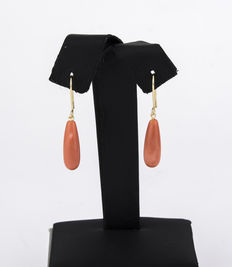 Yellow gold earrings with pear-shaped coral stone on each.