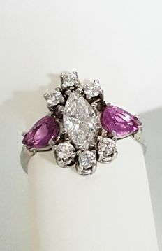 Gold cocktail ring set with diamonds and pink sapphire gemstones.