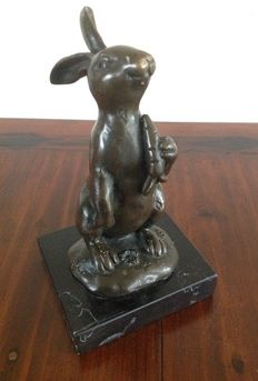 Bronze sculpture of a rabbit with a carrot on a black marble base