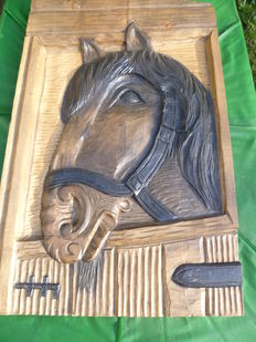 Wooden plaque of horse head.