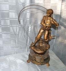 Atmospheric sculpture of a young man fishing on a marble base